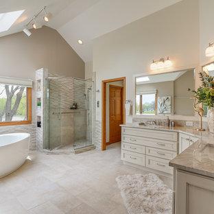 シカゴの大きいトランジショナルスタイルのおしゃれなマスターバスルーム (落し込みパネル扉のキャビネット、ベージュのキャビネット、置き型浴槽、コーナー設置型シャワー、分離型トイレ、ベージュのタイル、磁器タイル、ベージュの壁、磁器タイルの床、アンダーカウンター洗面器、珪岩の洗面台、ベージュの床、開き戸のシャワー) の写真