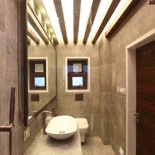 Kleines Modernes Duschbad mit Lamellenschränken, hellbraunen Holzschränken, Wandtoilette mit Spülkasten, grauen Fliesen, Steinfliesen, grauer Wandfarbe, Keramikboden und gefliestem Waschtisch in Pune