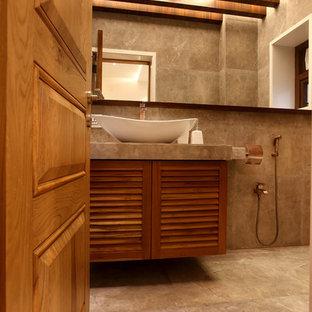 プネーの中サイズのコンテンポラリースタイルのおしゃれなバスルーム (浴槽なし) (ルーバー扉のキャビネット、中間色木目調キャビネット、分離型トイレ、グレーのタイル、石タイル、グレーの壁、セラミックタイルの床、タイルの洗面台) の写真