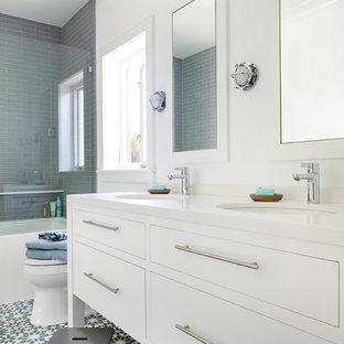 Diseño de cuarto de baño infantil, actual, pequeño, con armarios con paneles lisos, puertas de armario blancas, bañera empotrada, baldosas y/o azulejos blancos, baldosas y/o azulejos de vidrio, paredes blancas, suelo de azulejos de cemento, lavabo bajoencimera, encimera de cuarzo compacto, suelo azul, encimeras blancas y combinación de ducha y bañera