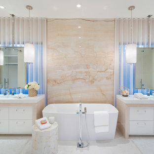 Example of a tuscan beige tile and stone slab white floor freestanding bathtub design in Orlando with flat-panel cabinets, white cabinets, an undermount sink and white countertops