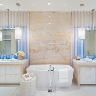 Foto på ett medelhavsstil vit badrum, med släta luckor, vita skåp, ett fristående badkar, beige kakel, stenhäll, ett undermonterad handfat och vitt golv