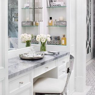 Cette image montre une salle de bain principale marine avec un placard avec porte à panneau encastré, des portes de placard blanches, un mur blanc, un plan de toilette en marbre, un sol multicolore et un plan de toilette multicolore.
