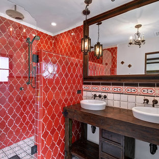 Example of a tuscan red tile and white tile alcove shower design in Orange County with dark wood cabinets, a vessel sink, wood countertops, a hinged shower door, brown countertops and furniture-like cabinets