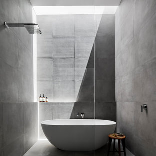 This is an example of a large contemporary master wet room bathroom in Melbourne with a freestanding tub, gray tile, porcelain tile, porcelain floors, grey floor, furniture-like cabinets, medium wood cabinets, a wall-mount toilet, grey walls, a drop-in sink, engineered quartz benchtops, an open shower and white benchtops.