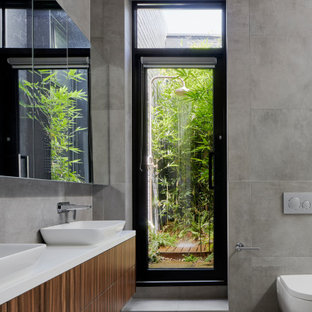 Large contemporary master wet room bathroom in Melbourne with medium wood cabinets, a wall-mount toilet, gray tile, porcelain tile, grey floor, white benchtops, furniture-like cabinets, a freestanding tub, grey walls, porcelain floors, a drop-in sink, engineered quartz benchtops and an open shower.