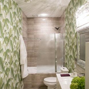 Foto de cuarto de baño con ducha, tropical, pequeño, con armarios con paneles lisos, puertas de armario de madera clara, bañera empotrada, sanitario de dos piezas, baldosas y/o azulejos grises, baldosas y/o azulejos de porcelana, paredes verdes, lavabo integrado y encimera de cuarzo compacto