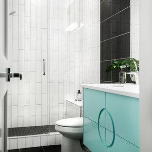 カルガリーの中サイズのミッドセンチュリースタイルのおしゃれなバスルーム (浴槽なし) (家具調キャビネット、ターコイズのキャビネット、黒いタイル、磁器タイル、ベージュの壁、磁器タイルの床、アンダーカウンター洗面器、珪岩の洗面台、グレーの床、開き戸のシャワー、アルコーブ型シャワー、一体型トイレ、白い洗面カウンター) の写真