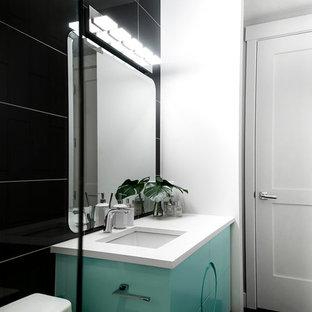 カルガリーの中サイズのミッドセンチュリースタイルのおしゃれなバスルーム (浴槽なし) (家具調キャビネット、ターコイズのキャビネット、黒いタイル、磁器タイル、ベージュの壁、磁器タイルの床、アンダーカウンター洗面器、珪岩の洗面台、グレーの床、開き戸のシャワー) の写真