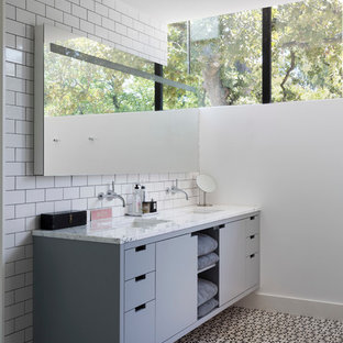 Inspiration for a modern white tile and subway tile bathroom remodel in Austin with an undermount sink, flat-panel cabinets and gray cabinets