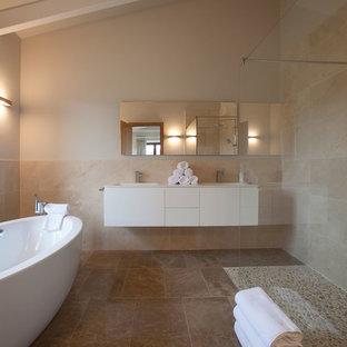Modelo de cuarto de baño marinero con bañera exenta, baldosas y/o azulejos beige, paredes beige, lavabo integrado, armarios con paneles lisos, puertas de armario blancas, ducha esquinera, suelo de baldosas tipo guijarro, suelo beige y encimeras blancas