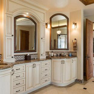 サンフランシスコの地中海スタイルのおしゃれなマスターバスルーム (レイズドパネル扉のキャビネット、大理石の洗面台、ブラウンの洗面カウンター、ベージュのキャビネット、マルチカラーのタイル、ベージュの壁、アンダーカウンター洗面器、マルチカラーの床) の写真