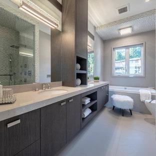 Idee per una stanza da bagno padronale minimal di medie dimensioni con ante lisce, ante marroni, doccia ad angolo, piastrelle a listelli, pareti grigie, porta doccia a battente, vasca da incasso, pavimento in gres porcellanato, lavabo sottopiano, pavimento grigio e top beige