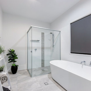 Design ideas for a contemporary master bathroom in Sunshine Coast with a freestanding tub, a corner shower, gray tile, white walls, grey floor and a hinged shower door.