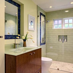 Foto di una piccola stanza da bagno con doccia design con lavabo integrato, ante lisce, ante in legno bruno, top in vetro, WC monopezzo, piastrelle verdi, piastrelle di vetro, pareti verdi, pavimento in pietra calcarea e porta doccia a battente