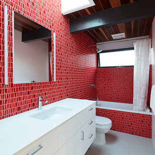 1950s 3/4 red tile gray floor bathroom photo in San Francisco with flat-panel cabinets, white cabinets, an undermount sink and white countertops
