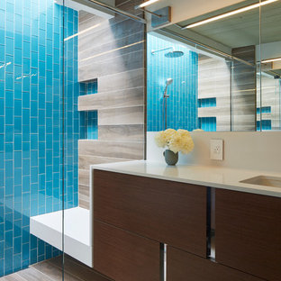 Design ideas for a midcentury bathroom in San Francisco with an undermount sink, flat-panel cabinets, dark wood cabinets, an alcove shower, blue tile, glass tile and white walls.