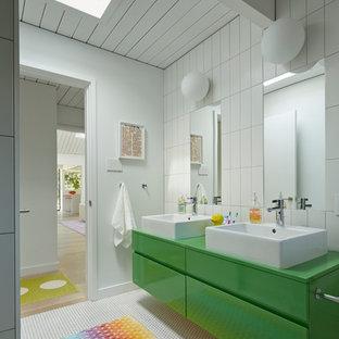 Foto på ett stort 50 tals badrum för barn, med ett fristående handfat, gröna skåp, mosaikgolv, släta luckor och vita väggar