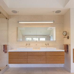 サンフランシスコの大きいコンテンポラリースタイルのおしゃれなマスターバスルーム (フラットパネル扉のキャビネット、中間色木目調キャビネット、置き型浴槽、アルコーブ型シャワー、壁掛け式トイレ、白いタイル、石タイル、白い壁、ライムストーンの床、壁付け型シンク、珪岩の洗面台、白い床、開き戸のシャワー、白い洗面カウンター) の写真