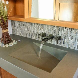 Immagine di una stanza da bagno padronale chic di medie dimensioni con lavabo integrato, ante lisce, ante in legno scuro, top in cemento, vasca da incasso, WC sospeso, piastrelle blu, piastrelle di vetro, pavimento in pietra calcarea e pareti blu