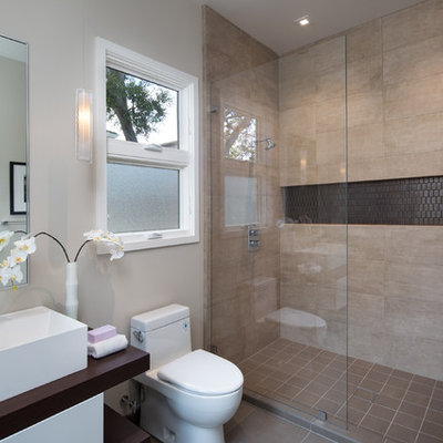 Example of a mid-sized trendy 3/4 beige tile and ceramic tile porcelain tile and brown floor alcove shower design in San Francisco with flat-panel cabinets, white cabinets, a one-piece toilet, white walls, a vessel sink, wood countertops, a hinged shower door and brown countertops