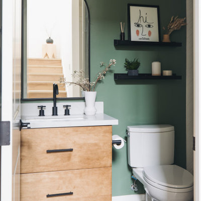 Inspiration for a small contemporary white tile and subway tile porcelain tile, black floor and single-sink bathroom remodel in San Francisco with flat-panel cabinets, medium tone wood cabinets, a two-piece toilet, green walls, an undermount sink, quartz countertops, a hinged shower door, white countertops and a floating vanity