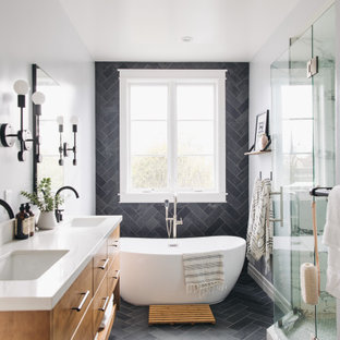 Photo of a mid-sized transitional master bathroom in San Francisco with flat-panel cabinets, medium wood cabinets, a freestanding tub, an alcove shower, a two-piece toilet, black tile, slate, grey walls, slate floors, an undermount sink, engineered quartz benchtops, black floor, a hinged shower door, white benchtops, an enclosed toilet, a double vanity and a floating vanity.
