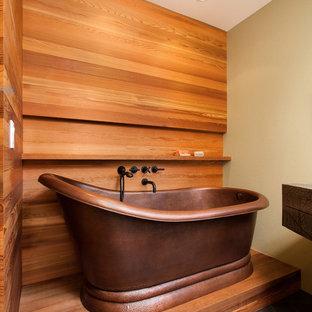 ロサンゼルスの中サイズのコンテンポラリースタイルのおしゃれなマスターバスルーム (フラットパネル扉のキャビネット、緑のキャビネット、置き型浴槽、分離型トイレ、オレンジの壁、一体型シンク、大理石の洗面台、スレートの床、黒い床) の写真