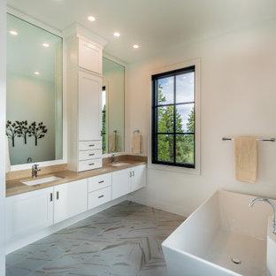 Inredning av ett klassiskt stort brun brunt badrum, med vita skåp, ett fristående badkar, vita väggar, bänkskiva i kvartsit, dusch med gångjärnsdörr, skåp i shakerstil, ett undermonterad handfat och grått golv