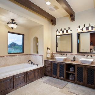 Ispirazione per una grande stanza da bagno padronale mediterranea con lavabo a bacinella, ante in stile shaker, ante in legno bruno, vasca da incasso, piastrelle beige, piastrelle in gres porcellanato, pareti beige, pavimento in gres porcellanato, top in granito e pavimento beige