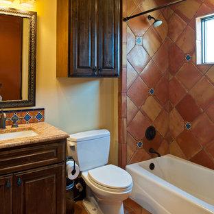 Aménagement d'une salle de bain sud-ouest américain avec un lavabo encastré, un placard avec porte à panneau surélevé, des portes de placard en bois sombre, une baignoire en alcôve, un combiné douche/baignoire, des carreaux en terre cuite, un sol en carreau de terre cuite et un carrelage marron.