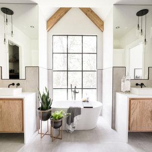 Foto på ett lantligt vit badrum, med släta luckor, skåp i mellenmörkt trä, grå kakel, grå väggar, ett fristående handfat och grått golv