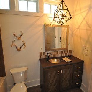 Esempio di una stanza da bagno stile rurale di medie dimensioni con ante a persiana, ante in legno bruno, vasca ad alcova, vasca/doccia e lavabo sottopiano