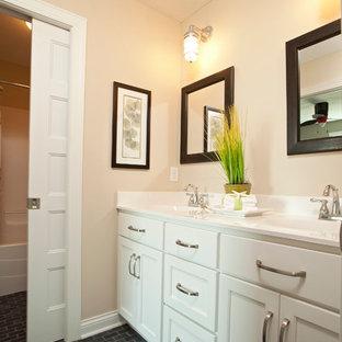 Diseño de cuarto de baño infantil, de estilo de casa de campo, de tamaño medio, con lavabo integrado, armarios con paneles lisos, puertas de armario blancas, baldosas y/o azulejos grises, baldosas y/o azulejos de piedra, encimera de acrílico, bañera empotrada, ducha empotrada, sanitario de dos piezas, paredes amarillas y suelo de pizarra