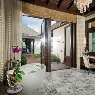 Inredning av ett exotiskt stort en-suite badrum, med möbel-liknande, skåp i mörkt trä, ett fristående badkar, vita väggar, klinkergolv i porslin, ett fristående handfat och granitbänkskiva