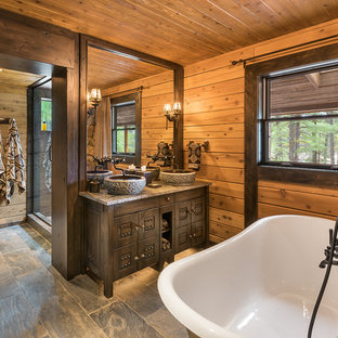 Bathroom - mid-sized rustic master slate tile slate floor and gray floor bathroom idea in Phoenix with a vessel sink, limestone countertops, furniture-like cabinets, dark wood cabinets and brown walls
