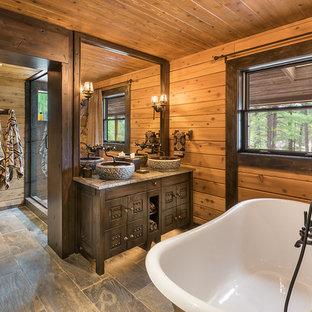 На фото: класса люкс главные ванные комнаты среднего размера в стиле рустика с ванной на ножках, душем в нише, плиткой из сланца, полом из сланца, настольной раковиной, столешницей из известняка, фасадами островного типа, темными деревянными фасадами, коричневыми стенами и серым полом