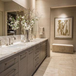 フェニックスの大きいコンテンポラリースタイルのおしゃれなマスターバスルーム (フラットパネル扉のキャビネット、グレーのキャビネット、置き型浴槽、コーナー設置型シャワー、一体型トイレ、ベージュのタイル、磁器タイル、ベージュの壁、磁器タイルの床、アンダーカウンター洗面器、珪岩の洗面台、ベージュの床、開き戸のシャワー、白い洗面カウンター) の写真