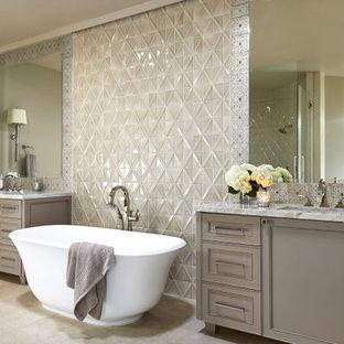 Foto di una stanza da bagno tradizionale con ante in stile shaker, ante grigie, vasca freestanding, piastrelle grigie, piastrelle di vetro, pareti grigie, lavabo sottopiano, pavimento beige e top grigio