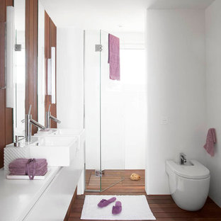 Immagine di una stanza da bagno con doccia design di medie dimensioni con lavabo a bacinella, ante lisce, ante bianche, doccia alcova, WC sospeso, piastrelle bianche, pareti bianche e parquet scuro