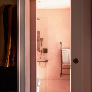 Foto de cuarto de baño principal, moderno, de tamaño medio, con armarios abiertos, ducha abierta, sanitario de pared, baldosas y/o azulejos rosa, baldosas y/o azulejos de cemento, paredes rosas, suelo de cemento, lavabo encastrado, encimera de cemento, suelo rosa, ducha abierta y encimeras rosas