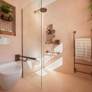 Diseño de cuarto de baño principal, minimalista, de tamaño medio, con sanitario de pared, paredes rosas, suelo de cemento, encimera de cemento, suelo rosa, ducha abierta, encimeras rosas, armarios abiertos, ducha abierta, baldosas y/o azulejos rosa, baldosas y/o azulejos de cemento y lavabo encastrado