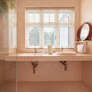 Imagen de cuarto de baño principal, minimalista, de tamaño medio, con armarios abiertos, ducha abierta, sanitario de pared, baldosas y/o azulejos rosa, baldosas y/o azulejos de cemento, paredes rosas, suelo de cemento, lavabo encastrado, encimera de cemento, suelo rosa, ducha abierta y encimeras rosas