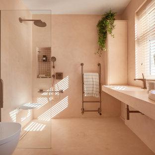 Imagen de cuarto de baño principal, moderno, de tamaño medio, con armarios abiertos, ducha abierta, sanitario de pared, baldosas y/o azulejos rosa, baldosas y/o azulejos de cemento, paredes rosas, suelo de cemento, lavabo integrado, encimera de cemento, suelo rosa, ducha abierta y encimeras rosas