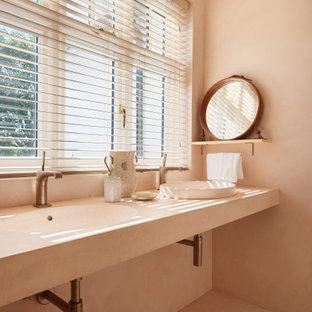 Imagen de cuarto de baño principal, moderno, de tamaño medio, con armarios abiertos, ducha abierta, sanitario de pared, baldosas y/o azulejos rosa, baldosas y/o azulejos de cemento, paredes rosas, suelo de cemento, lavabo encastrado, encimera de cemento, suelo rosa, ducha abierta y encimeras rosas