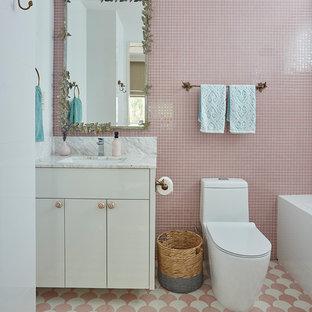 シンガポールのトランジショナルスタイルのおしゃれな子供用バスルーム (フラットパネル扉のキャビネット、白いキャビネット、ピンクのタイル、ピンクの壁、アンダーカウンター洗面器、ピンクの床、グレーの洗面カウンター) の写真