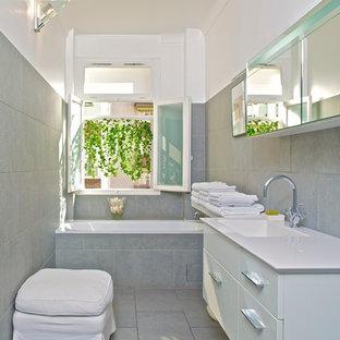 Aménagement d'une petite salle de bain principale contemporaine avec une baignoire en alcôve, un carrelage gris, un mur gris et un lavabo intégré.