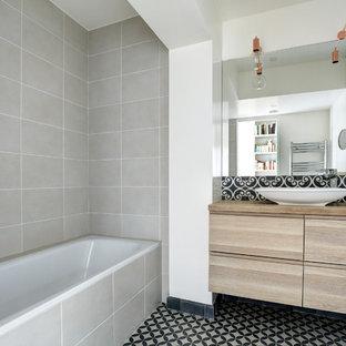 Inspiration pour une salle d'eau nordique avec un placard à porte plane, des portes de placard en bois brun, une baignoire posée, un carrelage gris, un mur blanc, une vasque, un plan de toilette en bois, un sol multicolore et un plan de toilette marron.