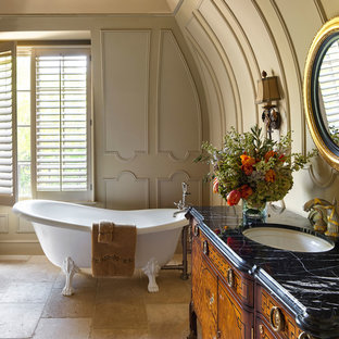Claw-foot bathtub - victorian master beige floor claw-foot bathtub idea in Minneapolis with furniture-like cabinets, medium tone wood cabinets, beige walls, an undermount sink, marble countertops and black countertops