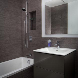 ニューヨークの中サイズのモダンスタイルのおしゃれな子供用バスルーム (フラットパネル扉のキャビネット、濃色木目調キャビネット、ドロップイン型浴槽、一体型トイレ、茶色いタイル、セラミックタイル、茶色い壁、セラミックタイルの床、一体型シンク、珪岩の洗面台、茶色い床、引戸のシャワー、白い洗面カウンター) の写真